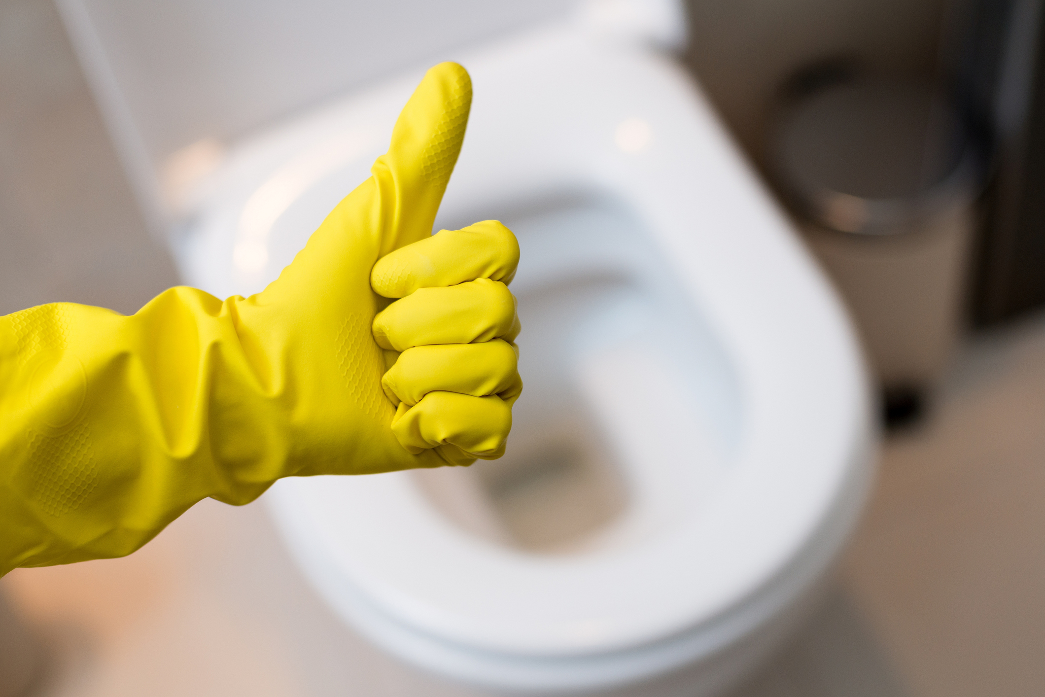 hand with glove showing thumb up sign against clean toilet